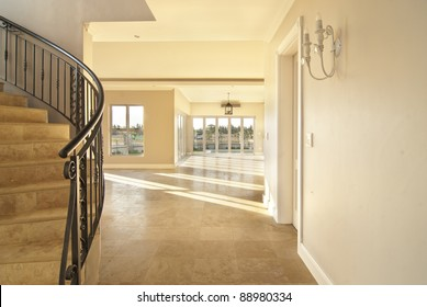 Staircase and empty lounge of a modern house. Everything is tiles with sunlight coming through the windows