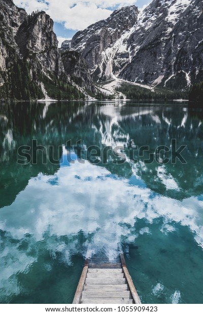 A staircase leading to the water in an mountain lake in the Dolomites. The shot was take in Lago di Braies, in South Tyrol, Italy.