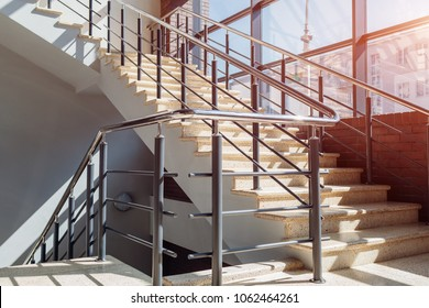 Staircase in modern buisness center building. Emergency exit. Stairs in shopping center. White ladder by window in hotel.