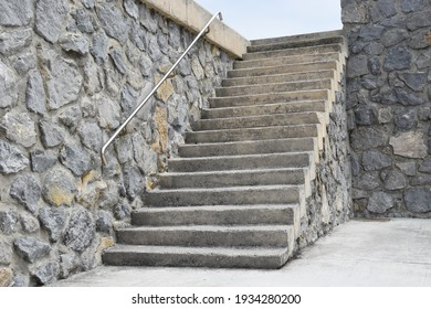 Staircase next to a rustic stone wall