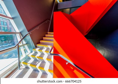 Staircase painted in red. Abstract fragment of urban architecture of modern luxury building, hotel, shopping mall, business center.   Interior design.