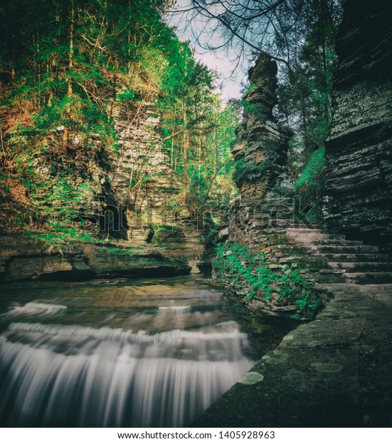 A staircase and rock formation next to a smooth waterfall at But