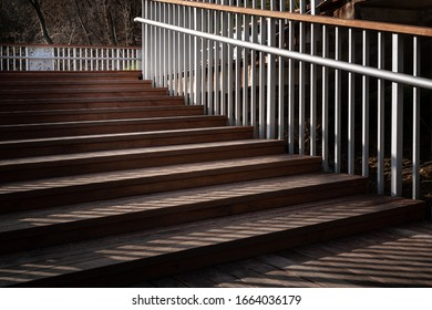 Staircase with a shadow from the railing. Go back down the ladder with wooden steps and metal railing. The play of light and shadow in the evening. Conceptual image.