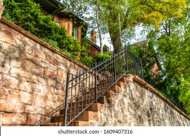 Staircase with stone treads and metal railing at the facade of a brick home