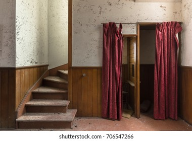 A staircase and a tattered confessional booth in an old abandoned church
