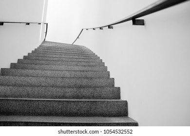 Staircase upwards between wlls in monochrome architectural background.