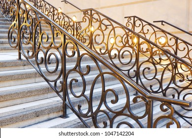 A staircase with a wrought iron  and Railing decorated with light colored lights.