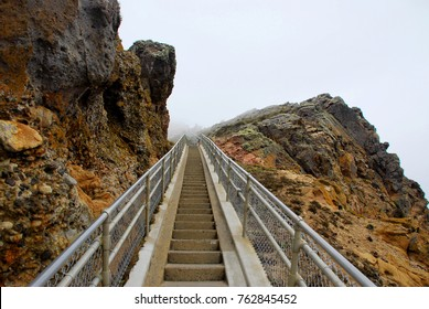 Stairs ascend from the Pacific Ocean into the fog at Point Reyes Lighthouse in Marin County, California