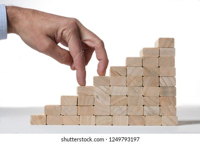 stairs build with wooden blocks on grey background with human finger climbing it