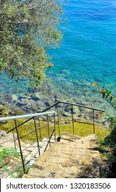 Stairs down to the sea with rocks on water in Europe Greece and green nature around
