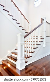 Stairs and glossy wooden floor of beautiful attractive luxury house with white walls having round window on top