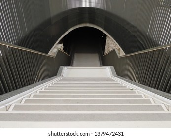 Stairs going down into a pedestrian tunnel under street. Light steps, pewter color railings all around, beige limestone wall at the bottom.