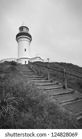 Stairs lead up to a lighthouse on top of a hill.