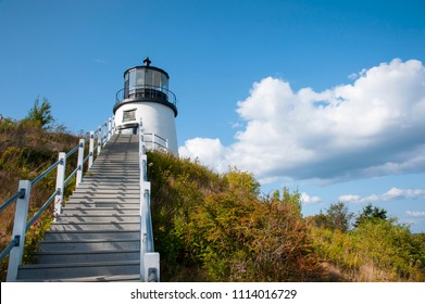 Stairs lead up to Owls Head lighthouse situated above a cliff on a summer day in Maine. It is a popular tourist attraction.
