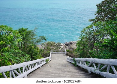 The stairs leading down to the blue sea beach.