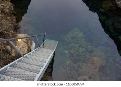 Stairs leading into a crystal clear, ancient glacial lake. Thingvellir, southwestern Iceland. A popular scuba diving spot.