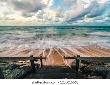 Stairs leading to the ocean on a tropical beach in Recife, Brazil. Long exposure of blue sea waves on a sandy beach at high tide, with a hint of color in the cloudy sky from the sunset.