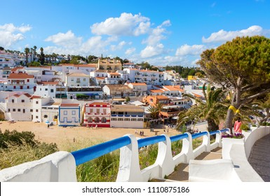 Stairs leading to the sandy beach surrounded by typical white houses,  Carvoeiro, Algarve, Portugal.