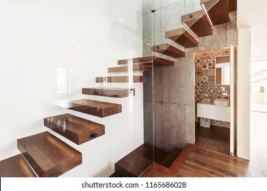 Stairs in living room with open door to bathroom and glass wall