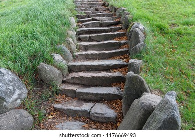 Stairs made by natural stones leading up through green vegetation.