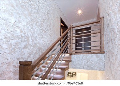 Stairs of oak with illumination and decorative plaster on the walls