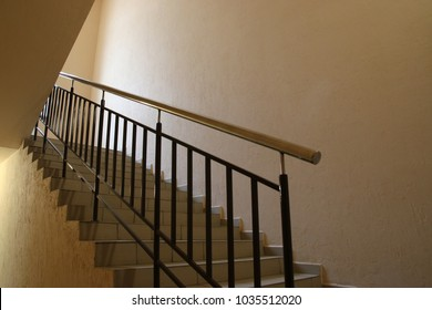 Stairs in office building. Design of handrails of stainless steel, railing rails of painted steel, tiled floors. Abstract steps, staircase march. Moving people between levels of multi-storey structure