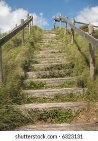 Stairs on a grassy dune lead up to a blue sky with clouds like a stairway to heaven.