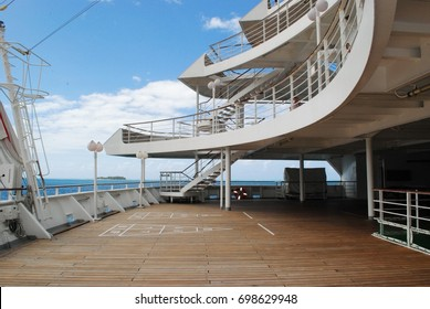 Stairs in an open deck in a cruise ship docked at a tropical island