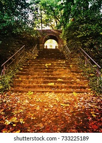 Stairs in a park leading outside through an underpass