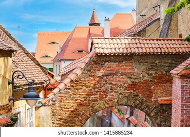 Stairs Passage in Sibiu, Romania. Top view of the arch and traditional houses with roofs and eye-like windows, on a bright day.