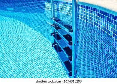 Stairs to the pool filled with clean water. Chrome plated surface.