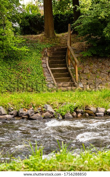 Stairs to the river. City park. Stone shore. Wooden balustrade. Foamed water.