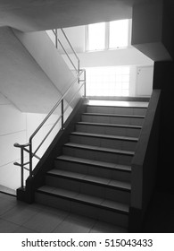 The stairs at the side of the lift are light from the window, white and black.