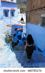 Stairway in the blue Medina of Chefchaouen, Morocco. Young brunette woman in a long dress walking down the stairs on the narrow streets of the Blue City, Morocco. Narrow colorful street in Chefchaouen