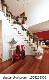 L'escalier est le point focal de cet intérieur joliment décoré d'une maison résidentielle.  Les lumières lumineuses et les arcs colorés sont festifs pour les fêtes de Noël.