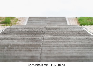 Stairway to heaven. Cultivated landscape with upward climbing stair stairs. Sea dike with green grass and cloudy clouds give way to the landscape