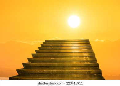 Stairway to heaven. Stairs towards sun on the orange sunset with clouds