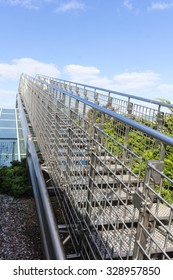Stairway to heaven - steel staircase going up to a blue sky with clouds