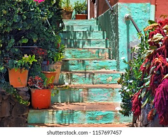 Stairway to a small house in the Canary Islands. The staircase is bright turquoise and on both sides are on each landing a flowerpot. Mediterranean ambience in the sunlight, colorful and idyllic.
