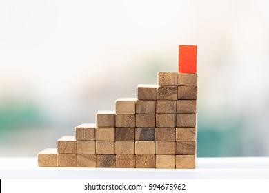 stairway of wood blocks with red block on top.