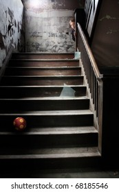 The Stairwell, a child peeks around the corner of the banister at the stairs littered with broken glass and a ball