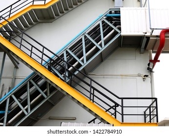Stairwell fire or emergency exit on wall of building with sunlight background. Fire escape stairs mounted to the outside.