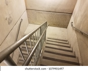 stairwell with metal railing and cement