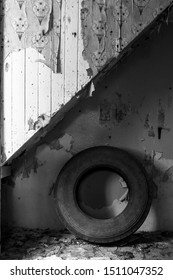 Stairwell in old derelict cottage with old truck tyre underneath it. Old wallpaper peeling from wood of stairwell and paint peeling from wall. In black and white.