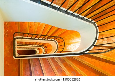 Stairwell with spiral staircase in hexagonal terracotta tiles with black rail