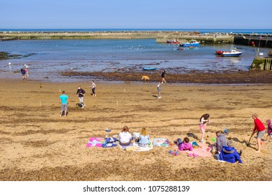 STAITHES, ENGLAND - APRIL 21: Families enjoying a hot sunny day on Staithes beach, North Yorkshire. In Staithes, England. On 21st April 2018.
