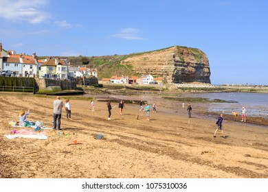 STAITHES, ENGLAND - APRIL 21: Family playing beach cricket in Staithes, England. In Staithes, England. On 21st April 2018.