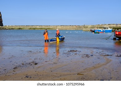 STAITHES, ENGLAND - APRIL 21: Staithes fishermen dressed in traditional oilskins. In Staithes, England. On 21st April 2018.