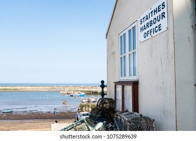 STAITHES, ENGLAND - APRIL 21: Staithes Harbour Office. Fishermen in distance on the beach. In Staithes, England. On 21st April 2018.
