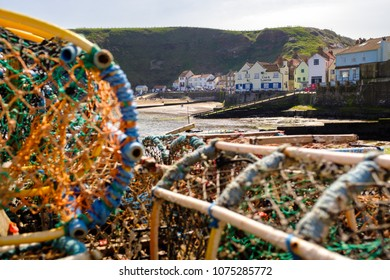 STAITHES, ENGLAND - APRIL 21: Lobster pots stacked in Staithes fishing harbour. In Staithes, England. On 21st April 2018.